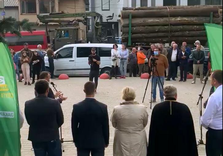 Голова Закарпатської ОДА виступає перед виборцями на фоні лісовозу