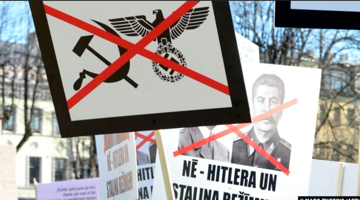 Плакати із засудженням нацизму і комунізму на акції у столиці Латвії. Рига, 16 березня 2013 року